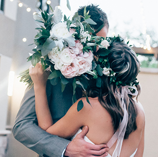 just married couple kissing behind bouquet